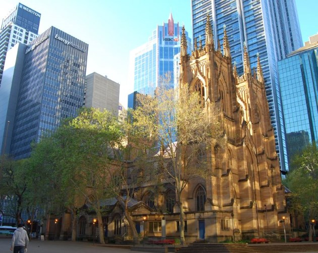 Reflected off the surrounding skyscrapers is the morning sun, colouring the sandstone of the Cathedral